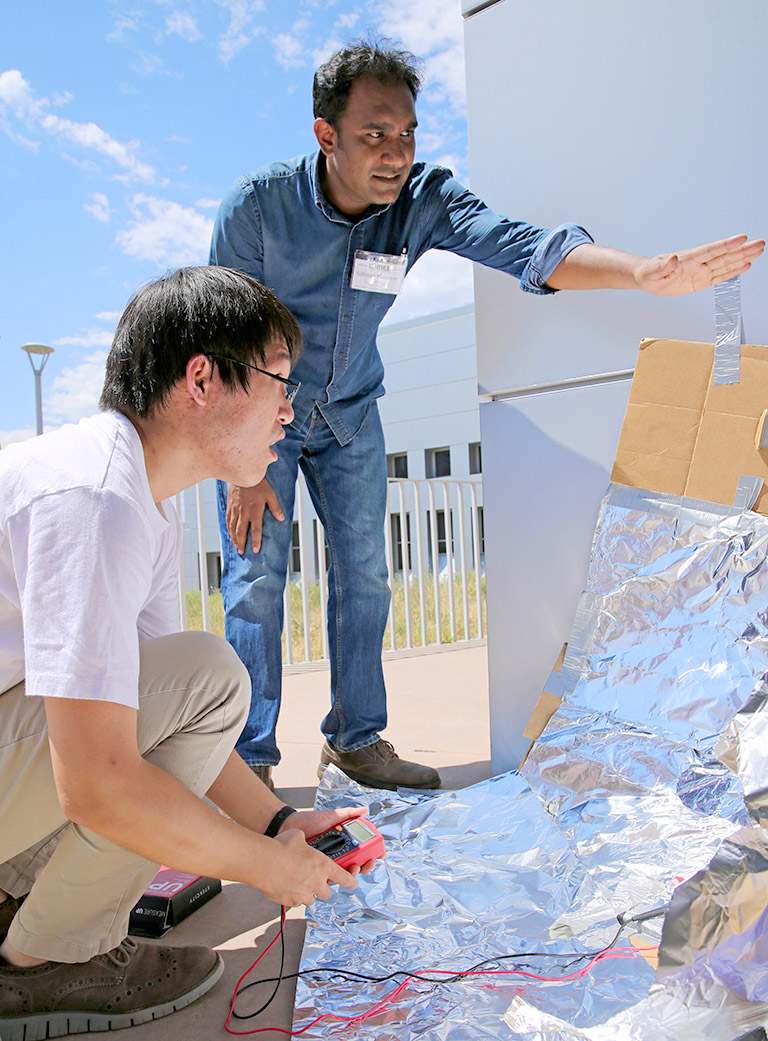 Two students, one standing, one crouching, examine a simple reflecting dish, made out of aluminum foil and cardboard. The dish is concentrating sunlight onto a solar cell, which one of the students is monitoring with a voltmeter.