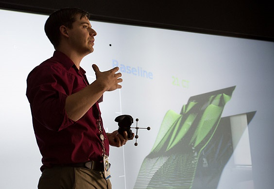 Photo of researcher standing next to abstract 3D image