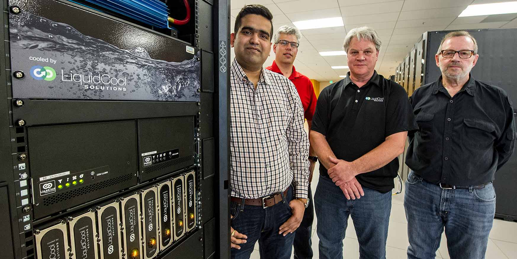 NREL researchers and LiquidCool Solutions representatives stand along-side LiquidCool's server cooling technology.