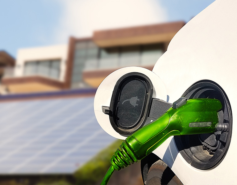 Photo of electric vehicle charging with solar panels in the background