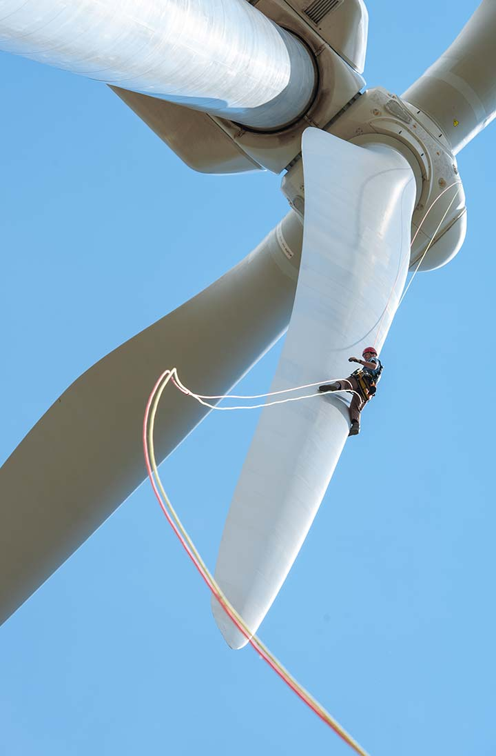 A worker repells down the blade of a large wind turbine