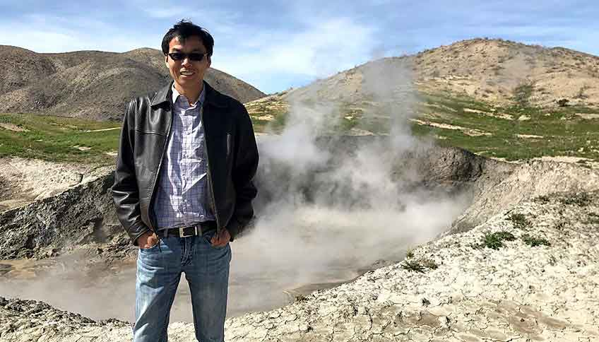 Guangdong Zhu stands in front of a hot spring, located near an active geothermal plant.