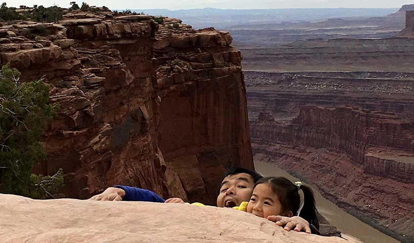Guangdong Zhu and his daughter pose for a photo next to a desert canyon, pretending to fall in.