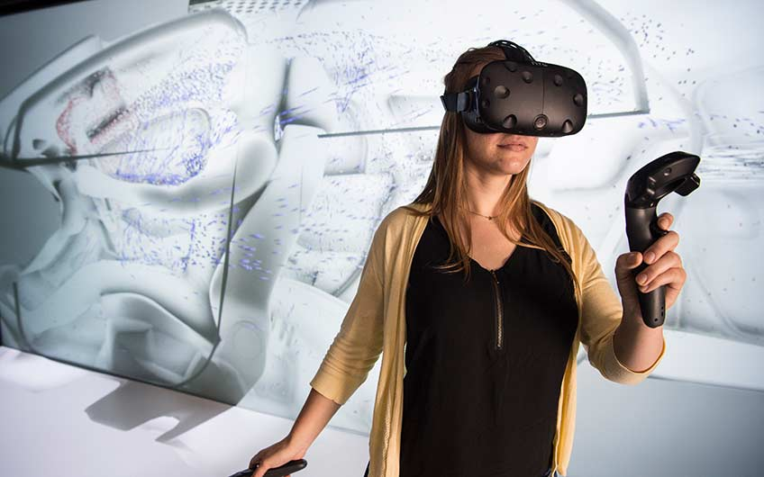 A woman wearing virtual reality glasses tests a simulation