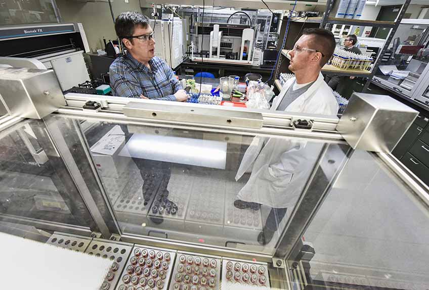 Two men speaking to each other with laboratory equipment surrounding them.