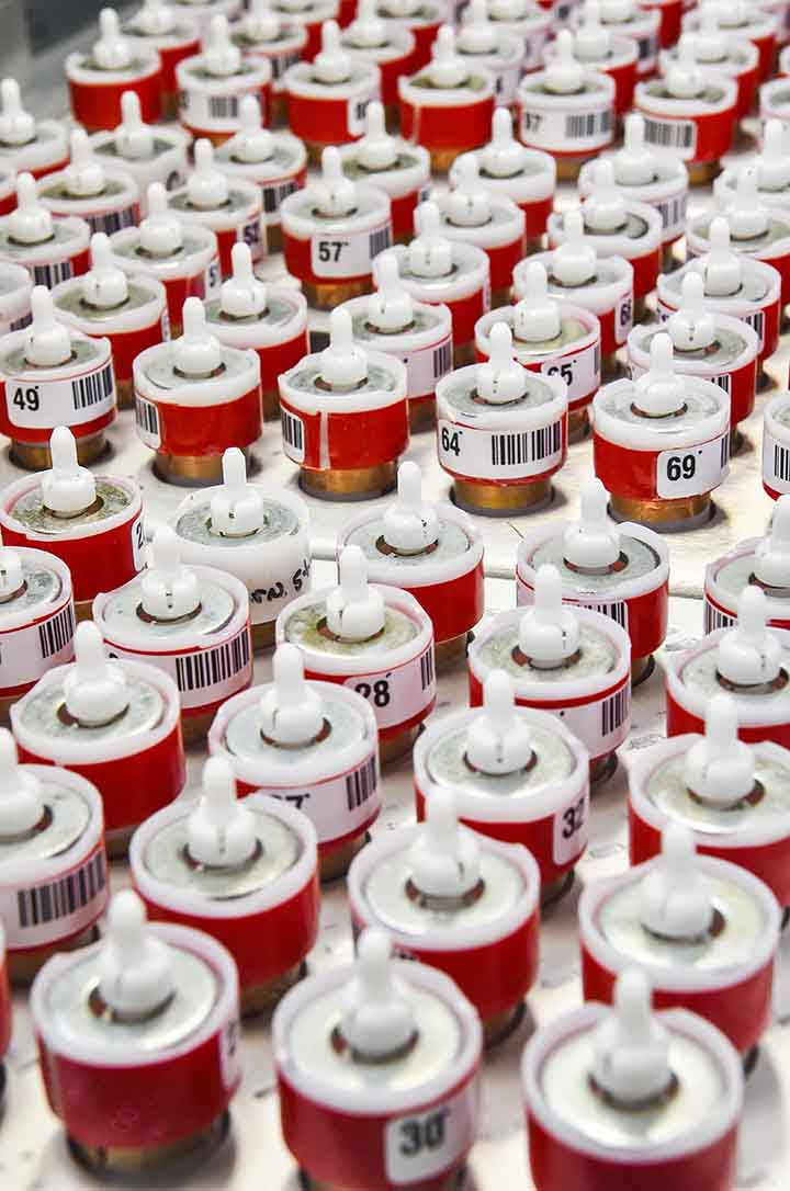 Small red cylindrical containers that are numbered and positioned in several rows.