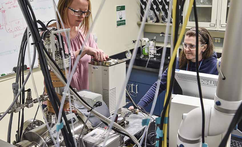 Two women working surrounded by laboratory equipment.