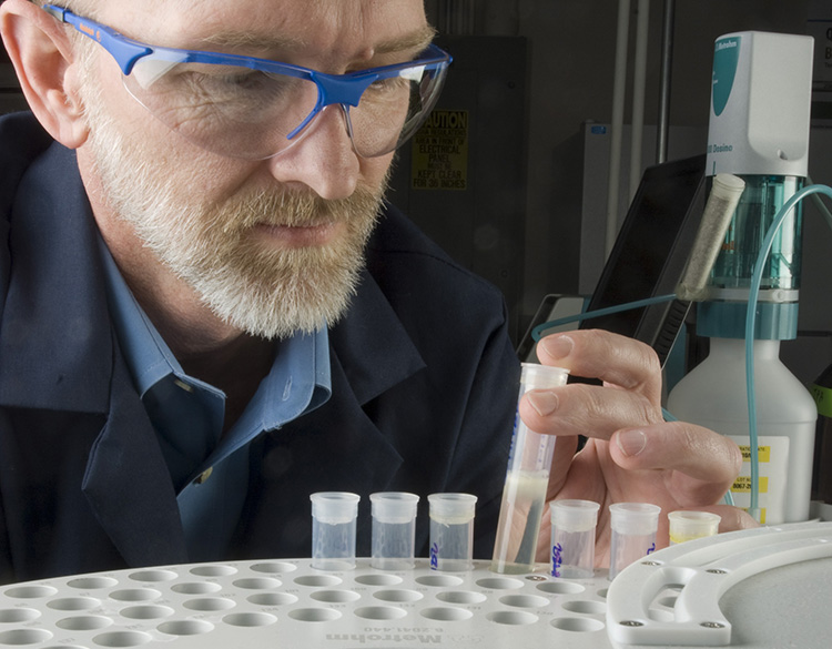 A man examines a biodiesel sample in NREL's Fuel Chemistry Laboratory.