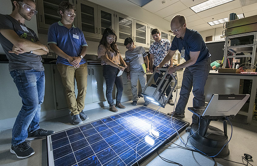 A group of students cluster around a PV module on the floor as an NREL scientist shines a light-camera combo on it, displaying the result on a nearby laptop. The goal is to visualize hidden cracks and defects in the panel.