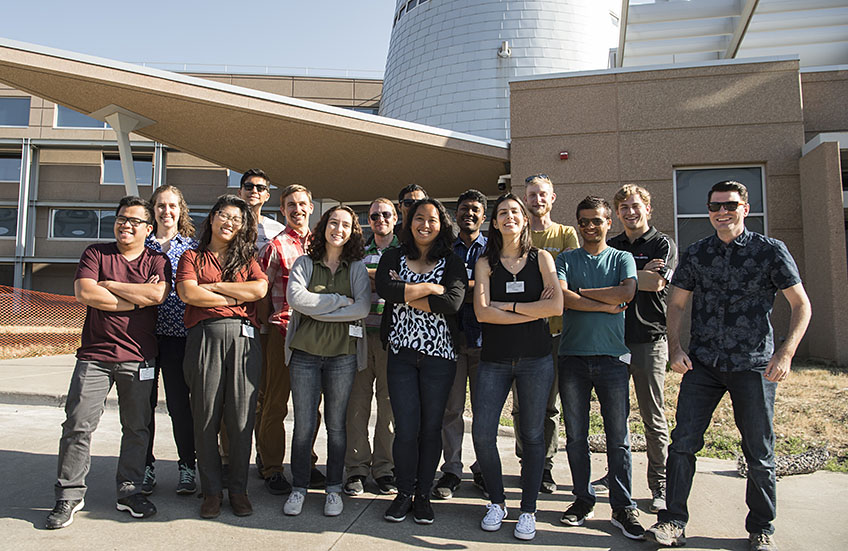 15 students pose as a group in front of one of NREL's lab buildings.