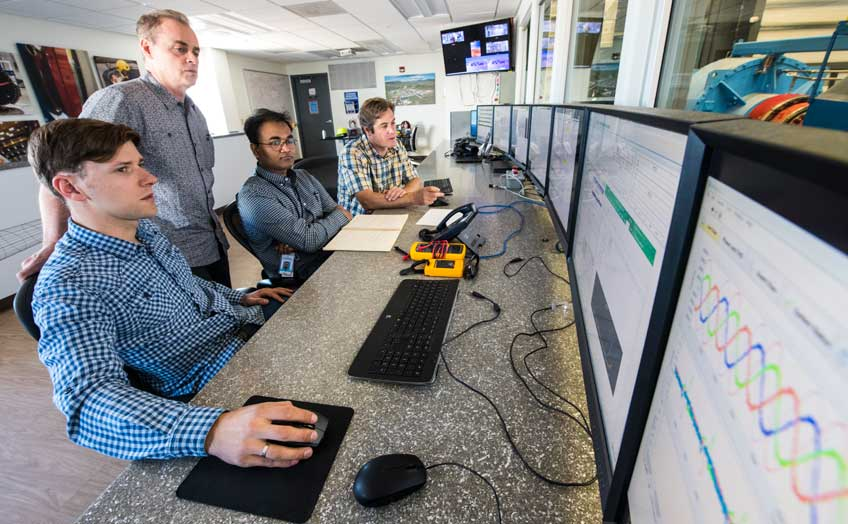Four men (one standing, three sitting) look at rows of computer monitors.