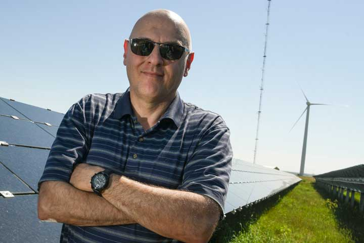 A man stands outside in front of a row of solar panels and near a wind turbine.
