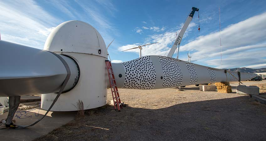 A turbine rotor sits perpendicular to the ground. One of the two visible blades has strips with dots along the length of it. A crane, two other turbines, and two meteorological towers are in the background.