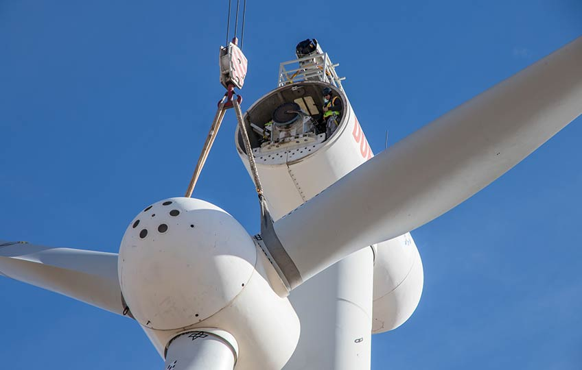 A three-bladed rotor hub is suspended from straps on a crane hook several feet below the turbine nose. A worker in safety vest, helmet, and safety glasses watches from the open nacelle.