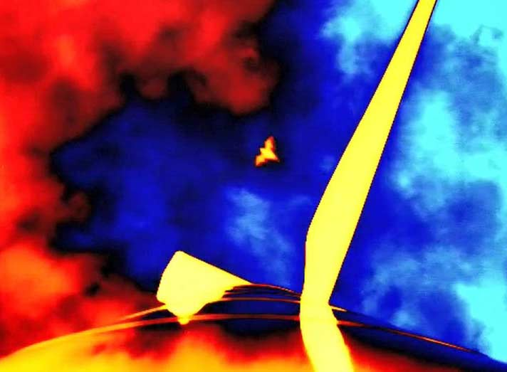 Thermal image looking up at the nacelle of a wind turbine. There is one blade pointing in the upper right of the image and a bat approaching in the center