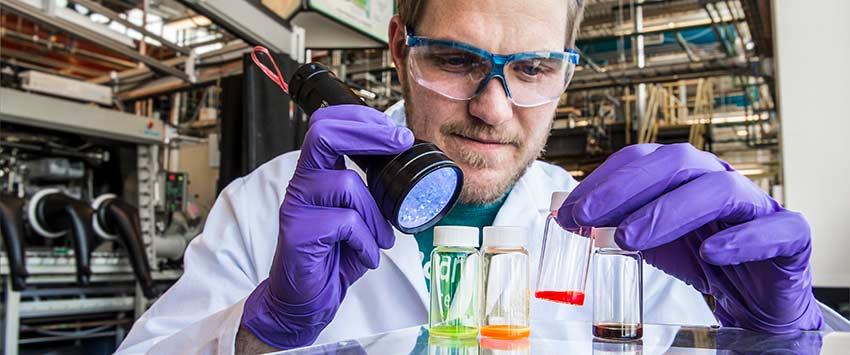 Christians works with vials of brightly colored perovskite quantum dot solutions at the National Renewable Energy Laboratory.