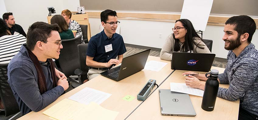 Photo of four students smile as they discuss ideas for the mini-hackathon challenge at NREL.