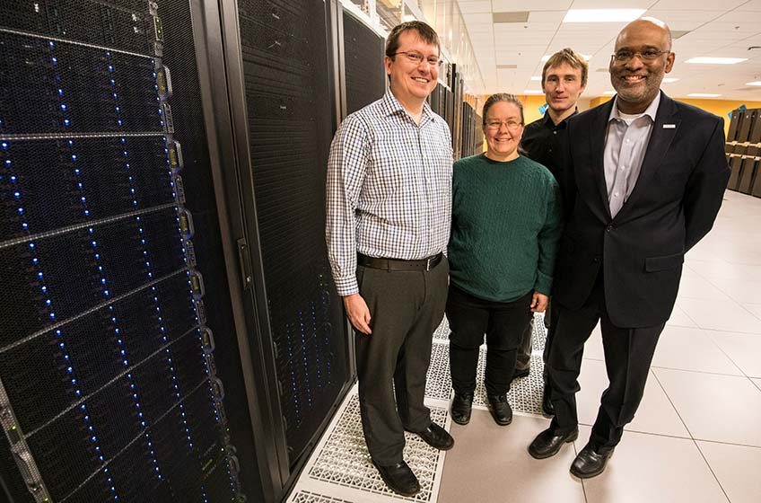 Four people stand next to a supercomputer.