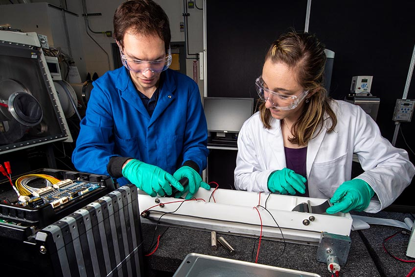 Photo of researchers in laboratory setting working with technical components.