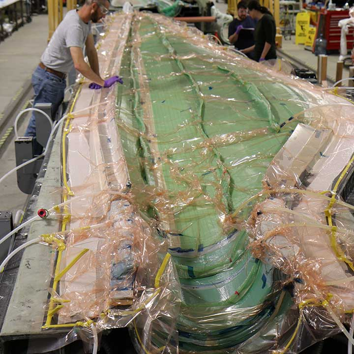A cross-section of a long wind blade covered in plastic. Three researchers work in the distance.