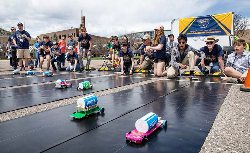 Model cars race down a track as a group of students cheer at a model electric car competition.