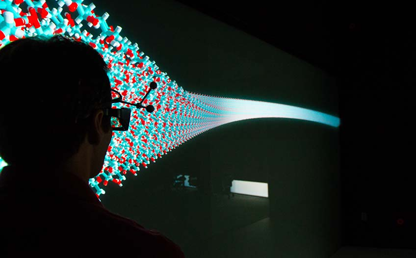 A man in 3D goggles looks at a large energy technology visualization in a dark room