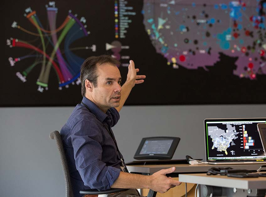 A man points to a projected data visualization of the U.S. power grid