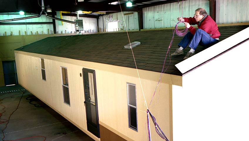 Ron Judkoff sits on the roof of a mobile home, working with a coil of wire.