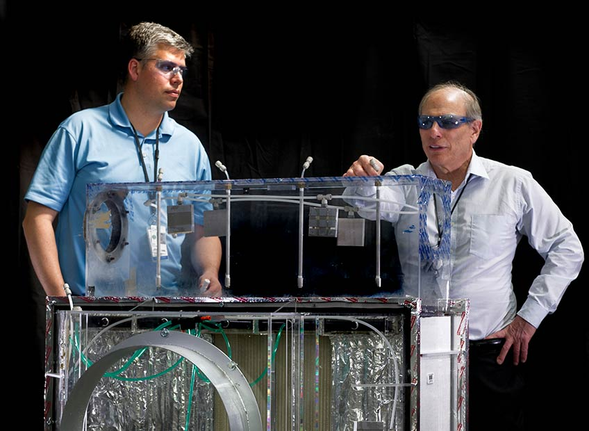 Ron Judkoff and Eric Kozubal stand wearing protective eyewear behind a piece of experimental HVAC equipment.
