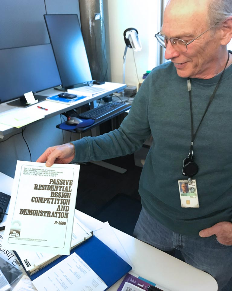 "Ron Judkoff stands in an office holding a copy of a manual titled ""Passive Residential Design Competition and Demonstration."""