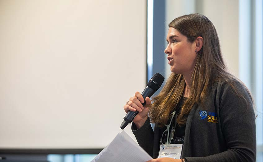 Rachel Romero speaks into a microphone in a jacket with a Solar Decathlon logo.