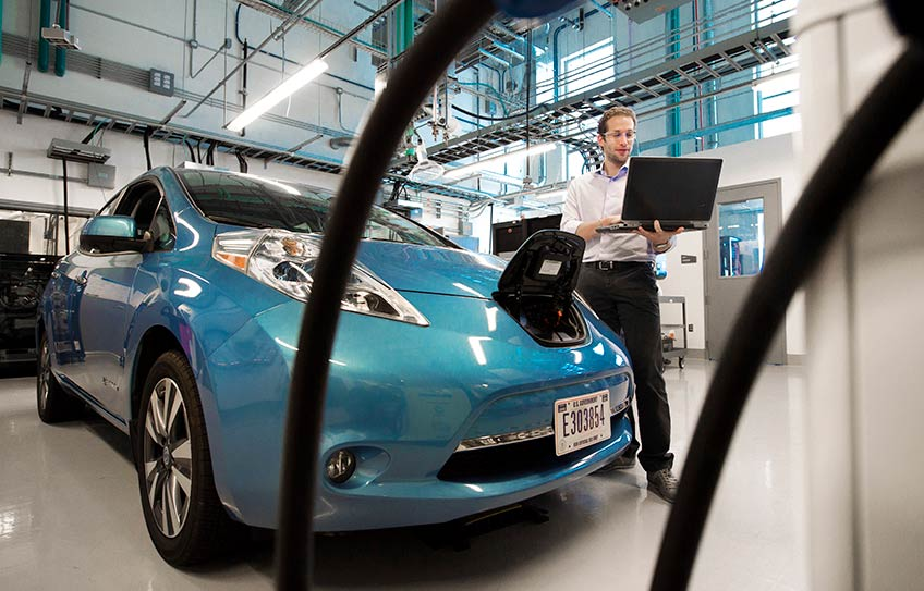 Man standing in lab garage looking at his laptop, standing next to an electric vehicle with charging cables in the foreground.