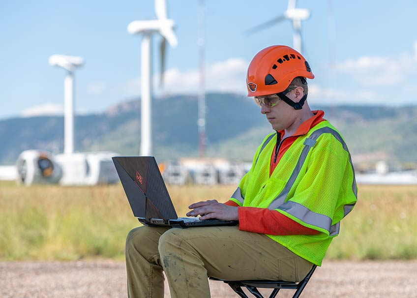 A researcher in a yellow safety vest and orange helmet types on a laptop outside with wind turbines in the distance.