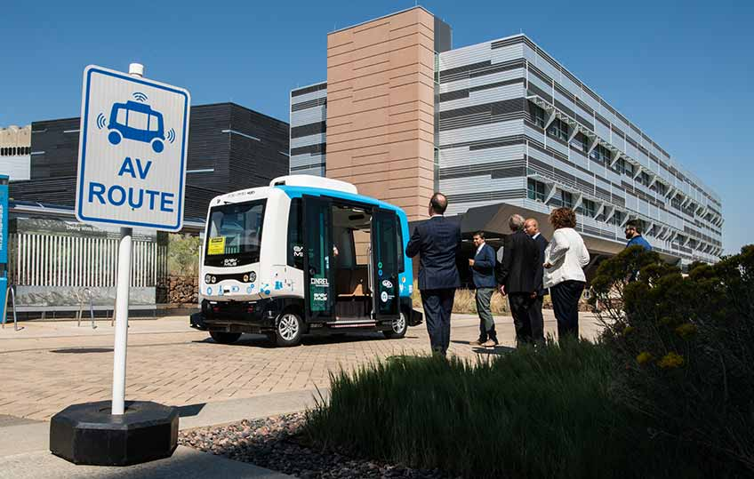 NREL employees line up outside to board the EasyMile automated electric shuttle on the NREL campus.