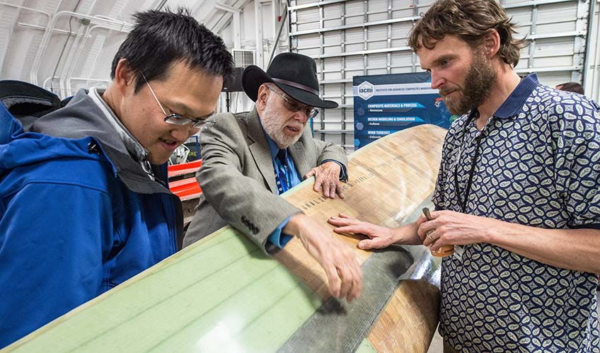 Three men examine a turbine blade manufactured in the CoMET.