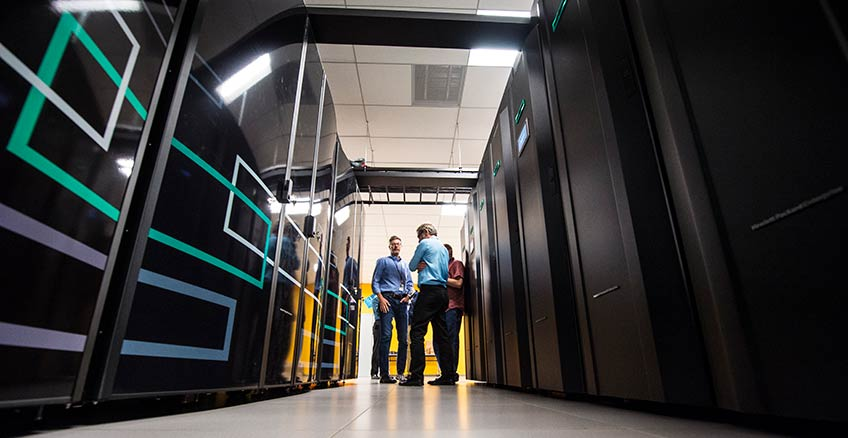 Three men stand between a row of computers in NREL's High Performance Computer Data Center.