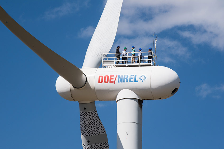 Photo of the top of a wind turbine, five people wearing hard hats are standing on top, blue skies with white clouds behind them.