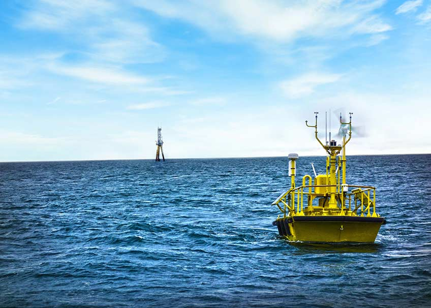 A yellow buoy floats on coastal blue waters with cloud streaked skies overhead.