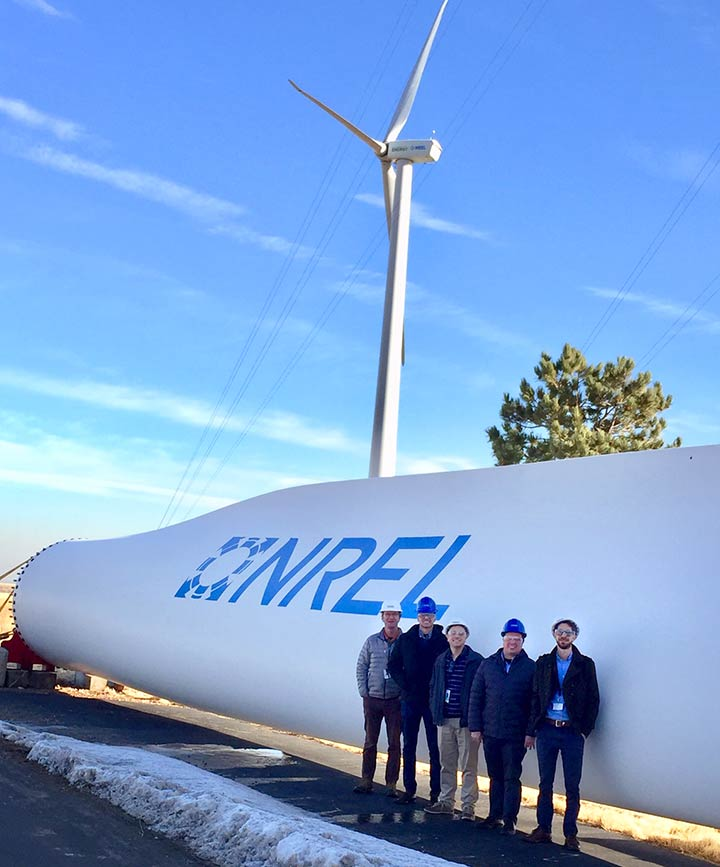 5 men wearing hard hats standing in front of a large wind turbine blade with the NREL logo.