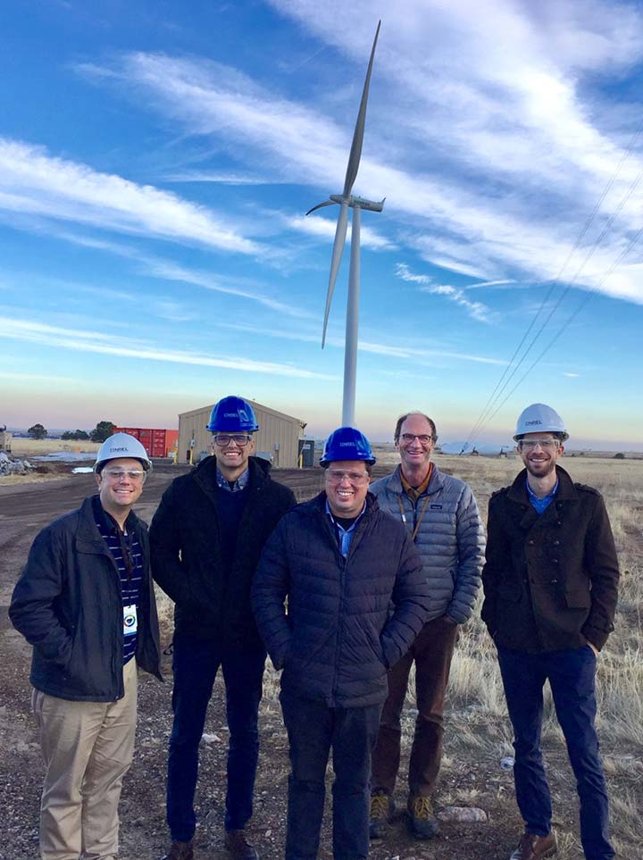 5 men standing in front of a wind turbine with their hands in their pockets (4 are wearing hard hats).