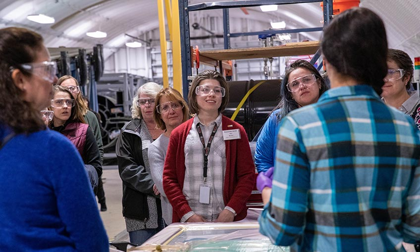 A group of women in the manufacturing industry listen as NREL research engineer Robynne Murray demonstrates an infusion process using thermoplastic resins.