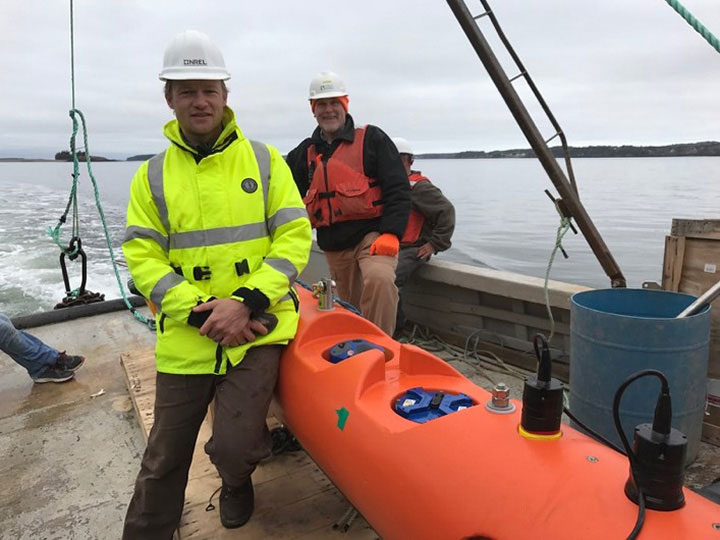 Researchers standing in front of marine energy equipment.
