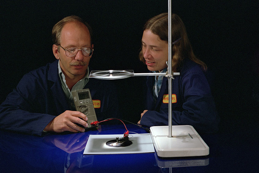 Two researchers hold a device to measure electrical output of a solar cell.