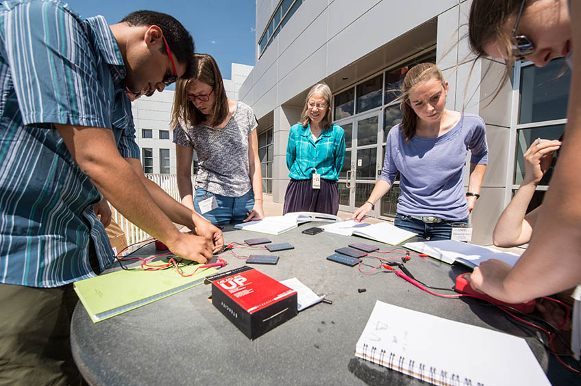 A researcher works with college students as they build solar cell concentrators.