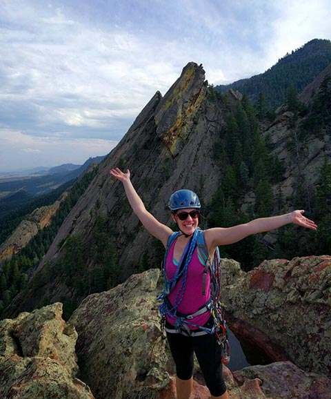 Photo of a woman rock climber at the top of a mountain with arms in the air after finishing a climb. Mountains in background.