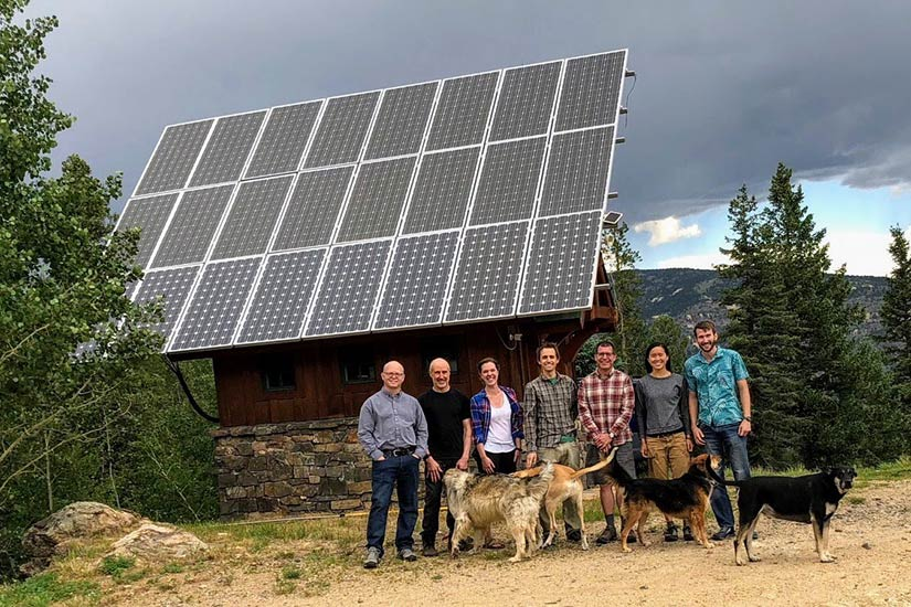 Photo of group of people with their dogs standing in front a cabin with big solar panels on the roof. Mountains in the background.