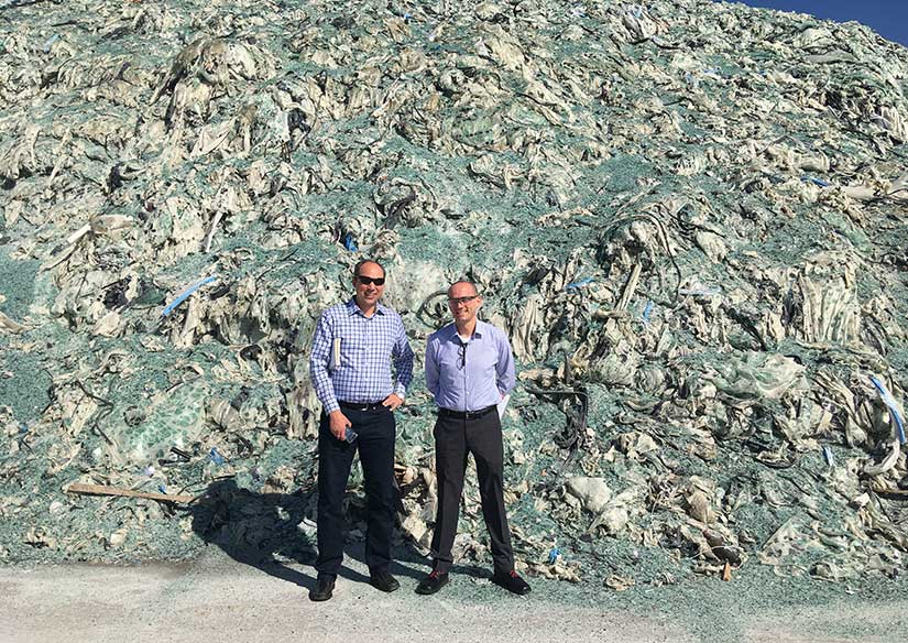 Photo of two men standing in front of a giant pile of trash.
