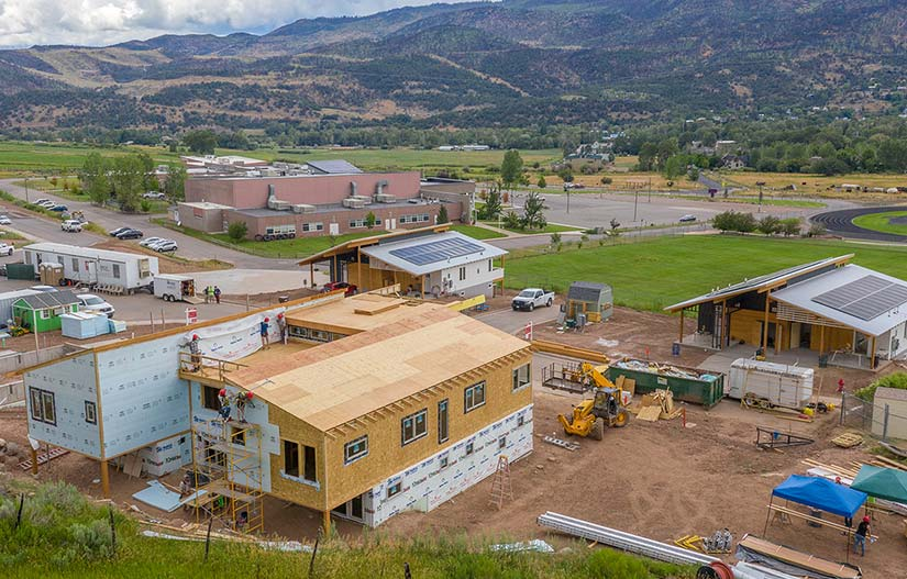 Photo of houses in a mountain neighborhood being constructed with built-in solar panels.
