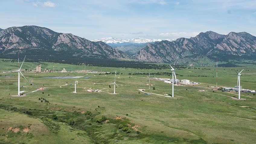 An aerial photograph of a energy laboratory campus with a wind turbine in the foreground and mountains in the background on a clear day.