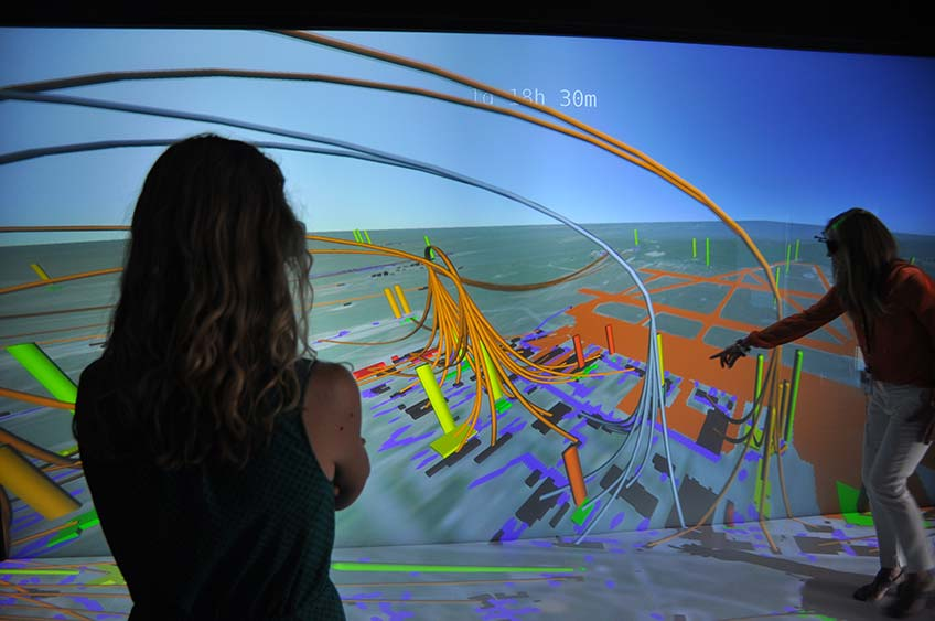 Photo of two women looking at a 3D visualization of data.